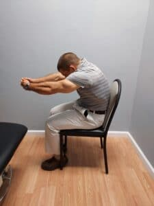 stretches for upper back pain between shoulder blades sitting reaching arms forward